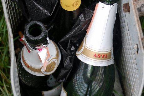 Tomme Martini Asti-flasker i en skraldespand.