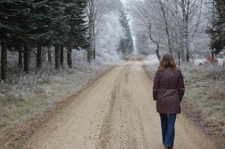 Malene går en tur i den frostklædte skov med ryggen til kameraet.