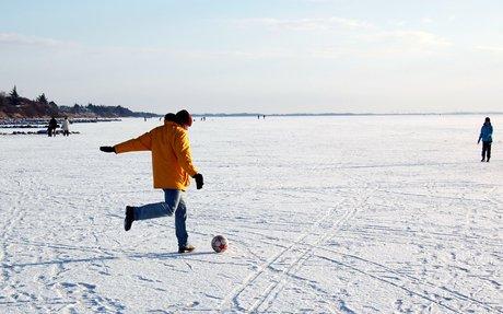 Far og søn spiller snebold på isen