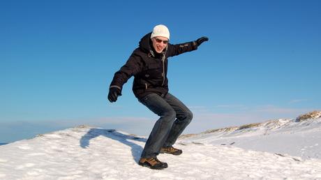 Ulrik står på toppen af en begravet bunker i Hvide Sande. Der er sne på bunkeren.